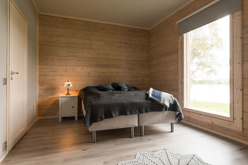 Master bedroom in a cosy wooden cottage by Rovaniemi Log House.