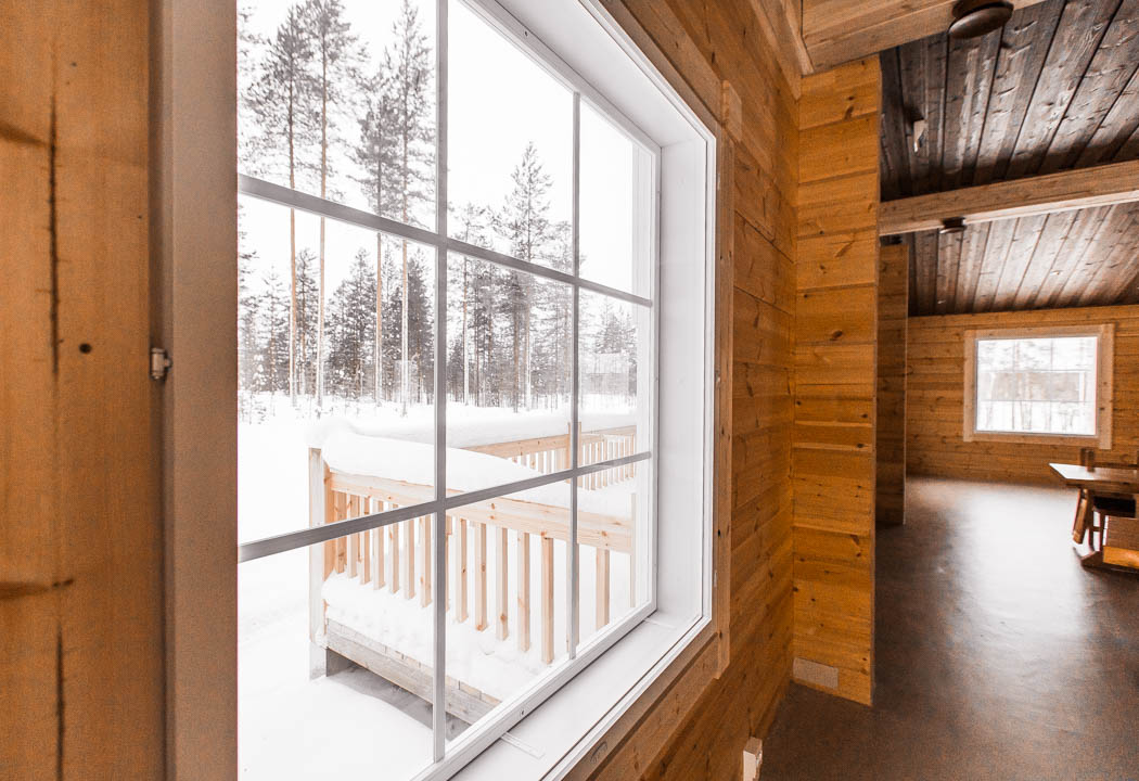 Safari house in Rovaniemi: Window view from a wooden log chalet.